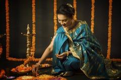 Retrato de la mujer india que celebra el festival de Diwali encendiendo la lámpara