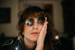 Retrato de la mujer joven aburrida con las luces y las gafas de sol llevadas imagen de archivo