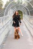 Retrato de la mujer joven alegre con su perro en el puente en parque Amistad, animal doméstico y ser humano fotos de archivo libres de regalías