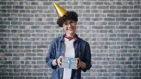 Retrato de la mujer joven alegre en la sonrisa brillante de la caja de regalo de la tenencia del sombrero del partido almacen de metraje de vídeo
