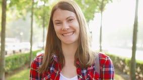 Retrato de la mujer joven alegre feliz que disfruta de la naturaleza El caminar en el parque verde que sonríe en la cámara metrajes