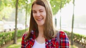 Retrato de la mujer joven alegre feliz que disfruta de la naturaleza El caminar en el parque verde que sonríe en la cámara almacen de metraje de vídeo