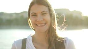 Retrato de la mujer joven alegre feliz que se relaja al aire libre Muchacha hermosa que mira la cámara y la sonrisa metrajes