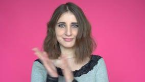 Retrato de la mujer joven de aplauso feliz sobre fondo rosado almacen de video