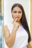 Retrato de la mujer joven atractiva con el finger en los labios Imagenes de archivo