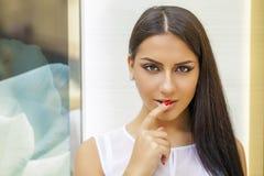 Retrato de la mujer joven atractiva con el finger en los labios Fotos de archivo libres de regalías