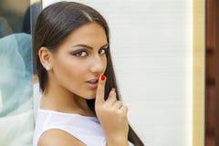 Retrato de la mujer joven atractiva con el finger en los labios Foto de archivo libre de regalías