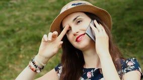 Retrato de la mujer joven atractiva con el sombrero del verano usando su Smartphone y la sonrisa al aire libre metrajes