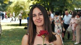 Retrato de la mujer joven atractiva con las rosas en su mano en el acontecimiento almacen de metraje de vídeo