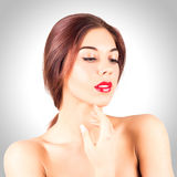 Retrato de la mujer joven atractiva con los labios rojos hermosos que miran abajo en fondo gris Mujer de la belleza con los labio Imágenes de archivo libres de regalías