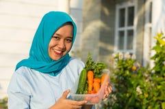 Retrato de la mujer joven atractiva del hijab que sostiene un cubo por completo de verduras delante de su casa imágenes de archivo libres de regalías