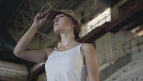 Retrato de la mujer joven atractiva en el uniforme militar que endereza el casquillo en su cabeza y que mira en la cámara y lejos almacen de metraje de vídeo