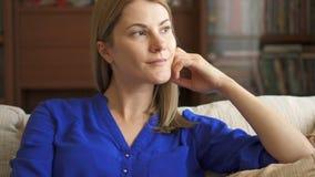 Retrato de la mujer joven atractiva hermosa en la blusa azul que se sienta en el sofá en el pensamiento de la sala de estar almacen de video