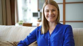 Retrato de la mujer joven atractiva hermosa en la blusa azul que se sienta en el sofá en la sonrisa de la sala de estar metrajes