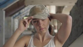 Retrato de la mujer joven atractiva que pone en el casquillo militar en su cabeza y que mira en la situación de la cámara en aban almacen de video