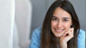 Retrato de la mujer joven atractiva que sonríe y que se relaja en un sofá en casa almacen de video