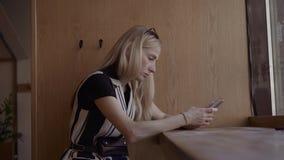 Retrato de la mujer joven atractiva que usa el teléfono elegante y comprobando la red social Dentro del café cerca de la ventana almacen de metraje de vídeo