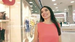 Retrato de la mujer joven bastante caucásica que disfruta de su paseo en alameda de compras metrajes