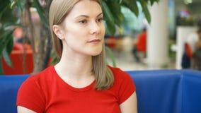 Retrato de la mujer joven bastante soñadora en la camiseta roja que se sienta en el pensamiento del café Árbol azul del verde del almacen de metraje de vídeo