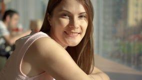 Retrato de la mujer joven bastante soñadora que se sienta en la tabla en café cerca de la ventana que piensa mirando la sonrisa d almacen de video