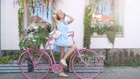 Retrato de la mujer joven de la belleza con la mochila y la bici rosada Forma de vida del concepto Florece la decoración metrajes