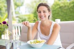 Retrato de la mujer joven de la belleza que come la ensalada Imagen de archivo libre de regalías