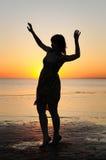 Mujer como silueta por el mar Imágenes de archivo libres de regalías