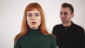 Retrato de la mujer joven con la boca grabada que sudenly quitar al papeleo y dar vuelta alrededor a un varón de griterío y grita metrajes