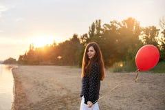 Retrato de la mujer joven con el balón de aire rojo que camina cerca de la orilla del mar tranquilo o del lago en puesta del sol  Imagen de archivo libre de regalías