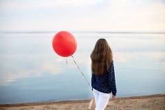 Retrato de la mujer joven con el balón de aire rojo y del actual bolso cerca de la orilla del mar tranquilo o del lago Las nubes  Fotos de archivo