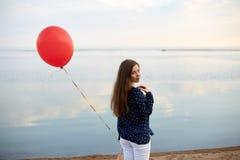 Retrato de la mujer joven con el balón de aire rojo y del actual bolso cerca de la orilla del mar tranquilo o del lago Las nubes  Imagen de archivo libre de regalías