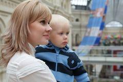 Retrato de la mujer joven con el niño en las manos. imagenes de archivo