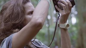 Retrato de la mujer joven con el pelo largo que sostiene la cámara y que toma las fotos almacen de metraje de vídeo