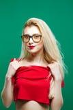 Retrato de la mujer joven con el pelo rubio largo, las lentes y los hombros desnudos en el top rojo que presenta en fondo verde a Fotos de archivo libres de regalías
