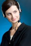 Retrato de la mujer joven con el receptor de cabeza, en el fondo azul, sonriendo Imágenes de archivo libres de regalías