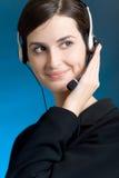 Retrato de la mujer joven con el receptor de cabeza, en el fondo azul, sonriendo Foto de archivo