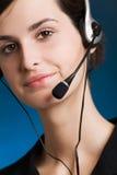 Retrato de la mujer joven con el receptor de cabeza, en el fondo azul, sonriendo Fotos de archivo libres de regalías