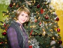 Retrato de la mujer joven con el regalo alrededor de un árbol de navidad adornado Muchacha en Año Nuevo del día de fiesta Imagen de archivo