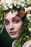 Retrato de la mujer joven con la decoración del pelo del pelo de las hojas, de las flores y de las mariposas en un fondo verde de imagen de archivo