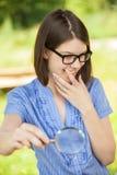 Retrato de la mujer joven con la lupa Imagen de archivo libre de regalías