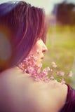 Retrato de la mujer joven con la parte posterior al aire libre de las flores Fotografía de archivo