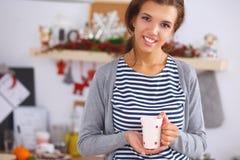 Retrato de la mujer joven con la taza contra cocina Fotos de archivo libres de regalías