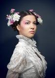 Retrato de la mujer joven con las flores frescas en pelo Foto de archivo
