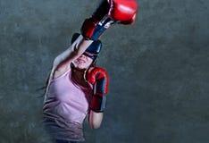 Retrato de la mujer joven con los guantes de boxeo que juegan al videojuego usando gafas de la realidad virtual de VR que simula  fotografía de archivo