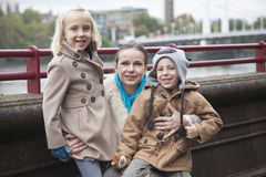 Retrato de la mujer joven con los niños que sonríen al aire libre Imágenes de archivo libres de regalías