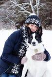 Retrato de la mujer joven con su perro blanco y negro en un fondo del bosque conífero del invierno imagenes de archivo