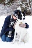 Retrato de la mujer joven con su perro blanco y negro en un fondo del bosque conífero del invierno fotos de archivo libres de regalías