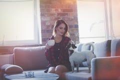 Retrato de la mujer joven con la taza de té o de café que se sienta en el sof Imágenes de archivo libres de regalías