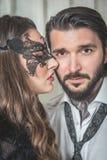 Retrato de la mujer joven con una máscara del cordón que toma el pelo a un hombre elegante como Imagen de archivo