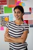Retrato de la mujer joven confiada contra notas pegajosas en oficina Imagenes de archivo
